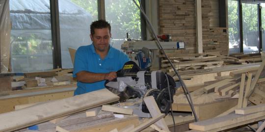 Jongere aan het werk met zaagmachine in houtwerkplaats